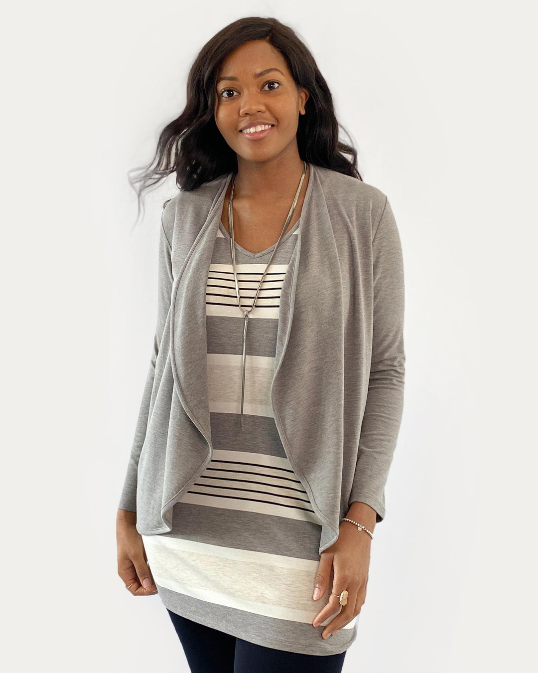 Woman wearing a grey cardigan over a striped top