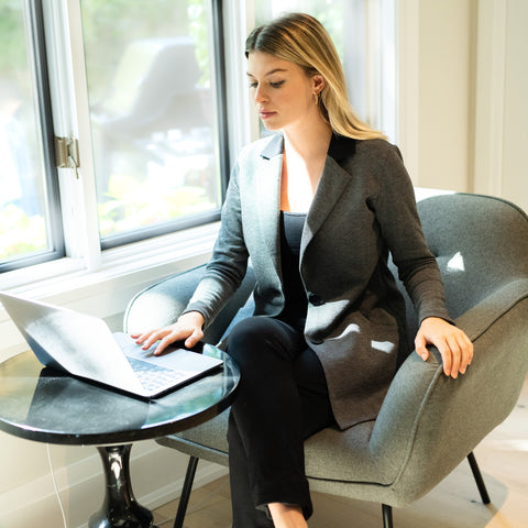 Woman in a blazer looking at a laptop