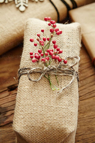Rectangular package wrapped in burlap tied with twine and decorative red berries