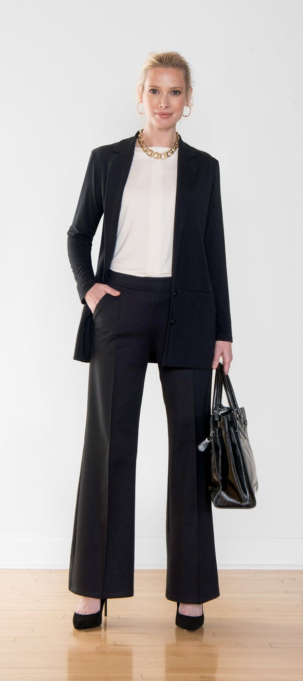 Woman wearing a professional suit, with a long black blazer and black wide leg pants