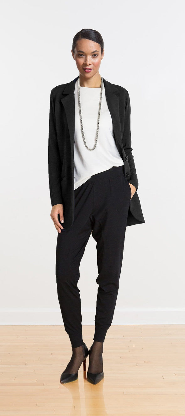 Casual women's outfit, with a long black blazer worn open over a white shirt and slouchy black pants