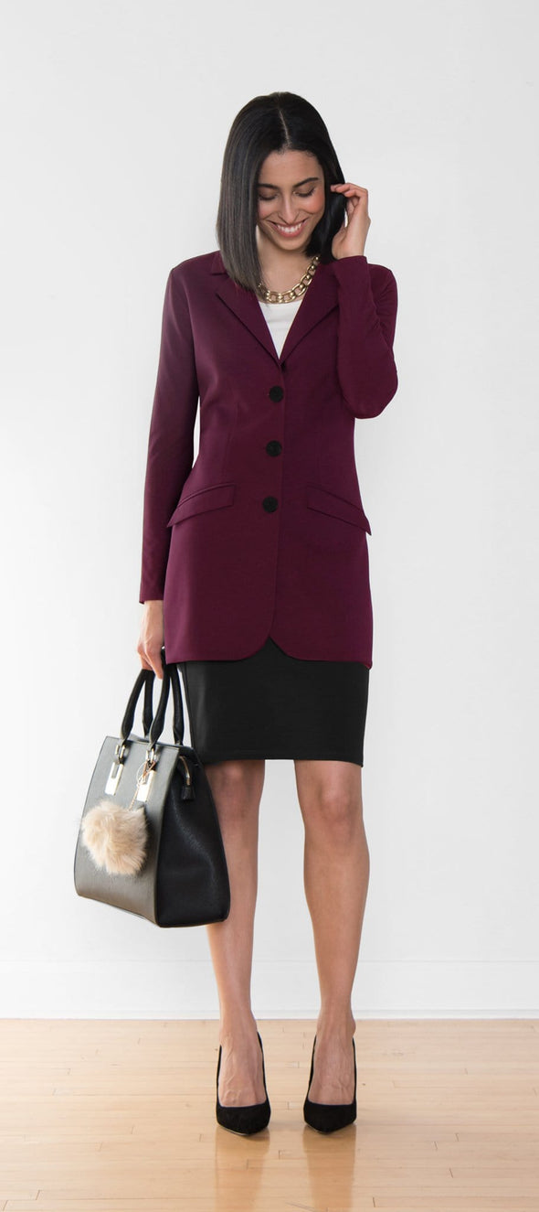 A long, reddish purple women's blazer worn with a short black skirt
