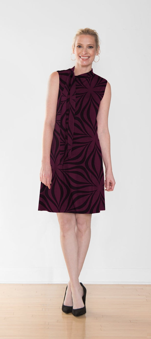 Woman wearing a sleeveless, knee-length dress in reddish purple with a black geometric pattern