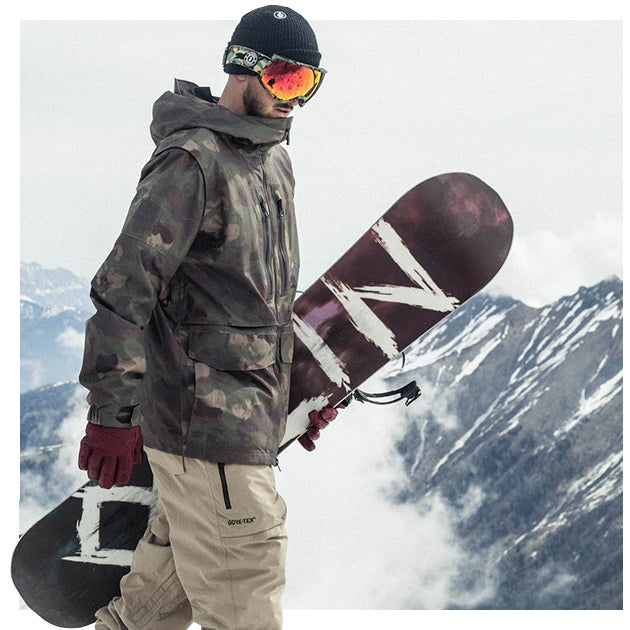 Male snowboarder holding his snowboard