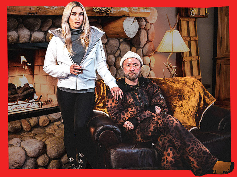 A man and a woman sitting in a winter lodge wearing Volcom outerwear.