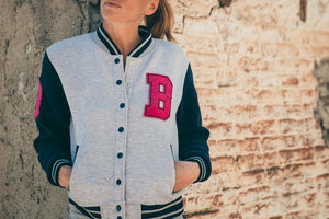 woman wearing light gray cotton varsity jacket