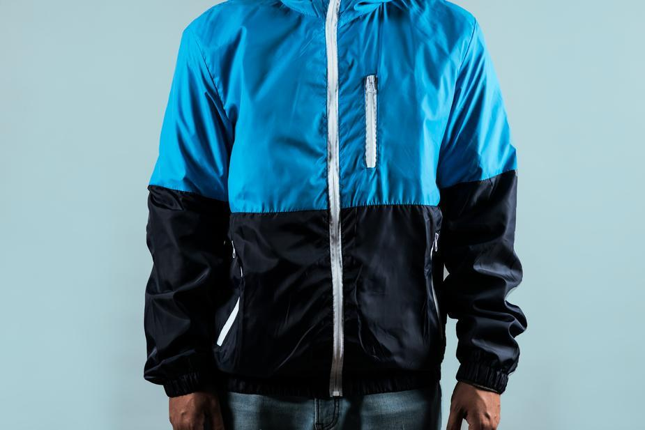 man wearing a half blue and half black zip up sport jacket