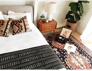 Bedroom with mud cloth and Kilim rugs