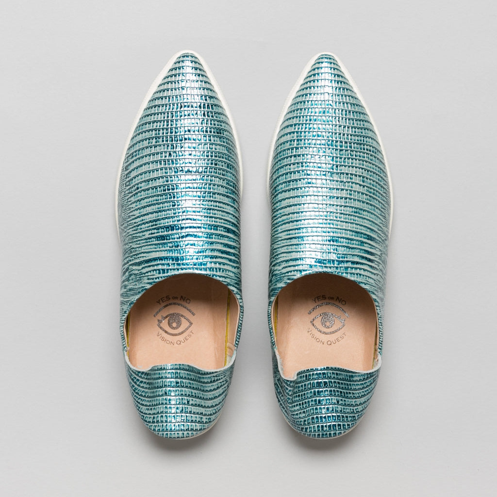 Overhead view of teal metallic lizard pattern leather babouche sneakers with pointy toes shown with the back heels folded down.