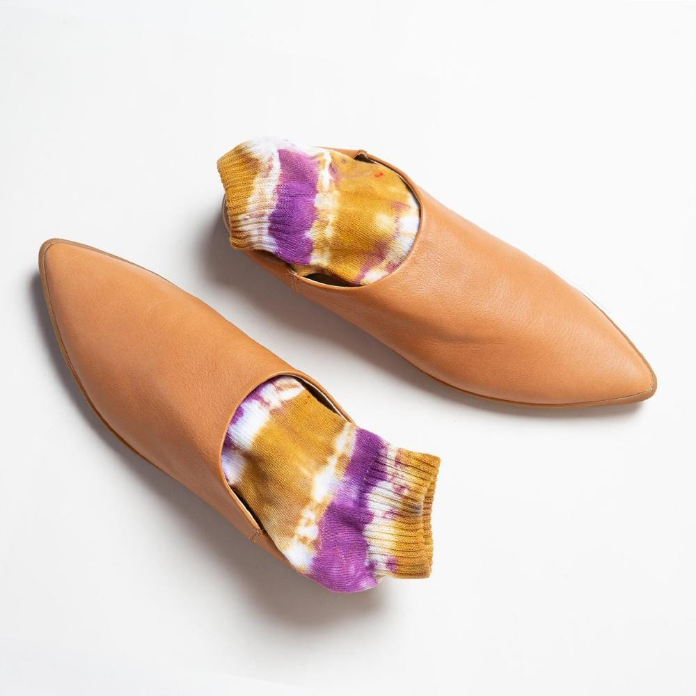 Overhead view of one pair of Vision Quest Shoes of butternut smooth leather babouche sneakers with pointy toes. Dark pink and golden yellow tie dyed socks are shown inside each shoe.