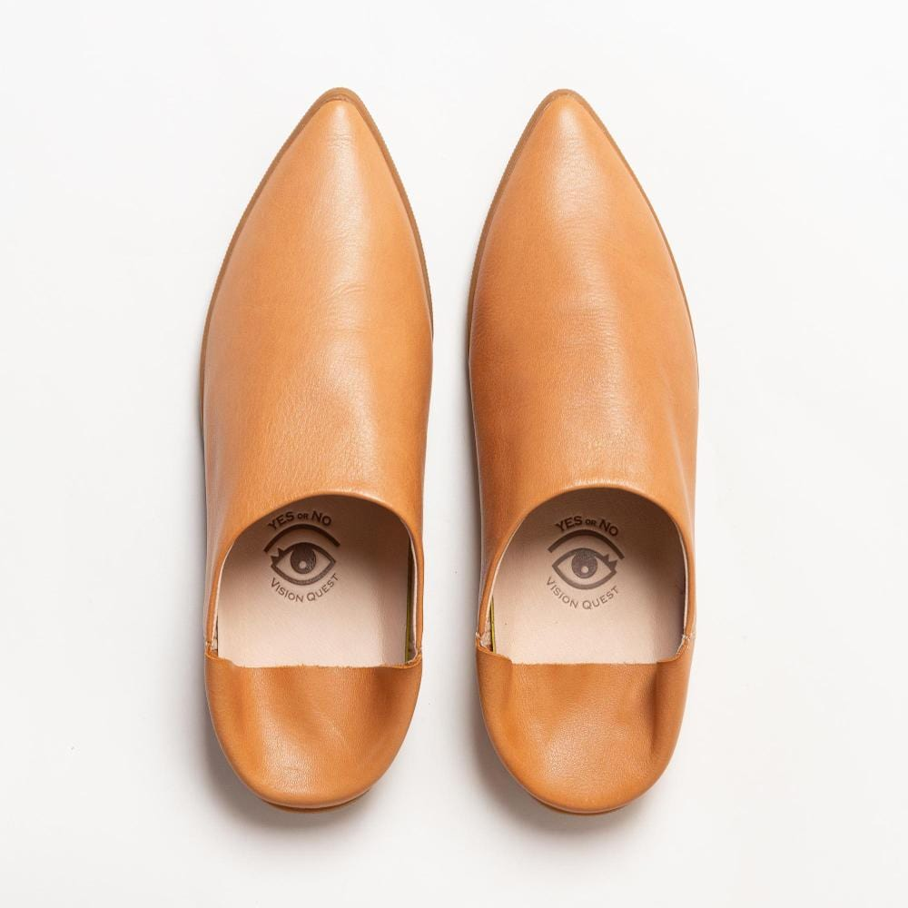 Overhead view of one pair of  butternut smooth leather babouche sneakers.  The toe shape of the shoes are pointy. Beige colored leather lining is visible with Vision Quest logo with one eye on each shoe, creating a pair of eyes together.