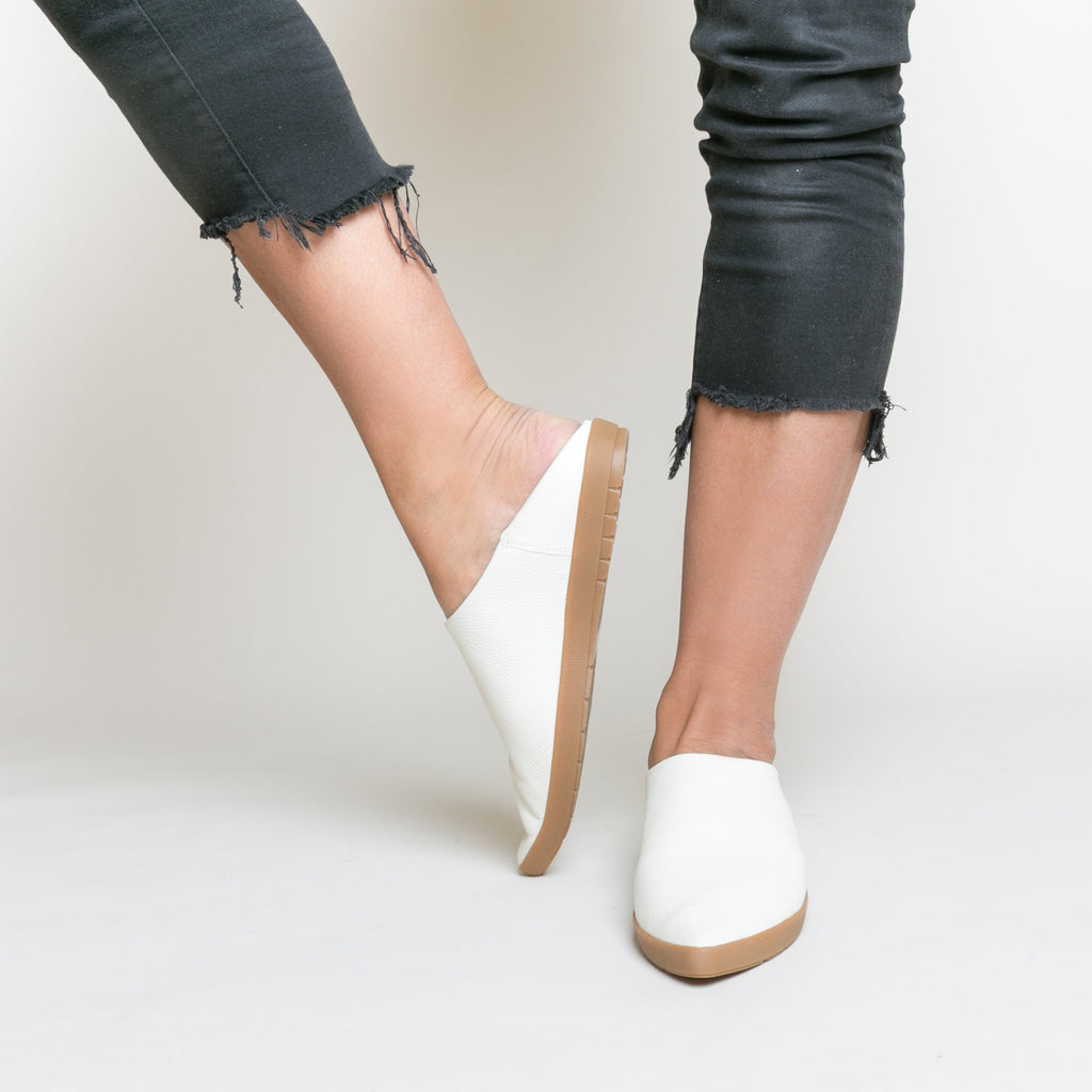 Creamy off white pebble grain leather babouche sneakers shown on legs wearing cropped black jeans without socks.  Bouncy rubber outsole in gum color.