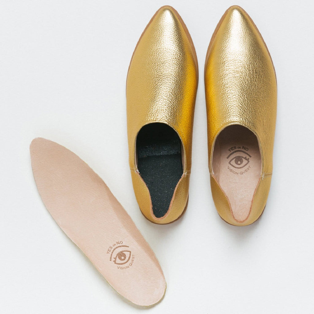 Restorative footbed insoles next to a pair of gold leather babouche sneakers from Vision Quest.