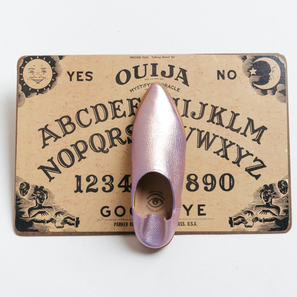 Overhead view of one Pink Prism leather babouche sneaker on a Ouija board.