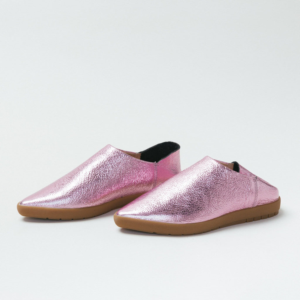 Profile view of Pink Prism leather babouche sneakers. One of the shoes features a folded back heel.