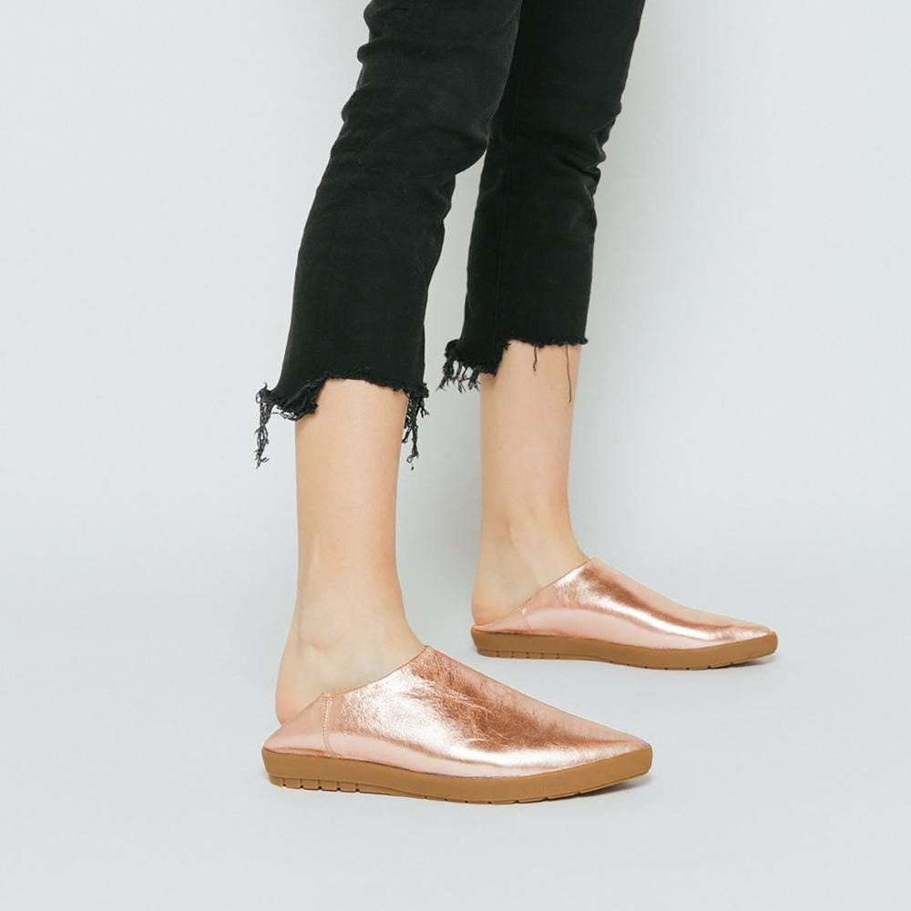 Vision Quest Shoes Rose gold metallic leather babouche shoes shown on legs with black denim cropped jeans.