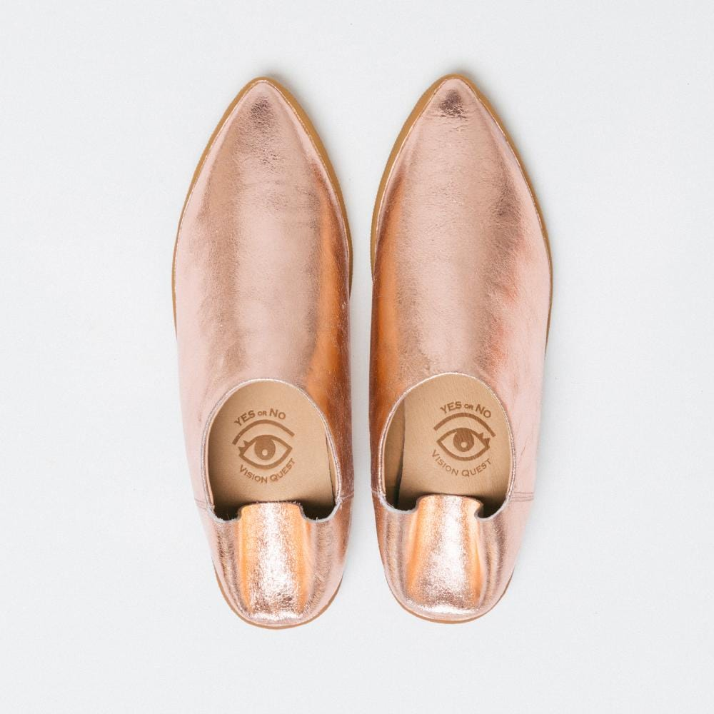 Overhead view of one pair of Vision Quest Shoes rose gold metallic babouche sneakers with pointy toes. the back heel folded down.