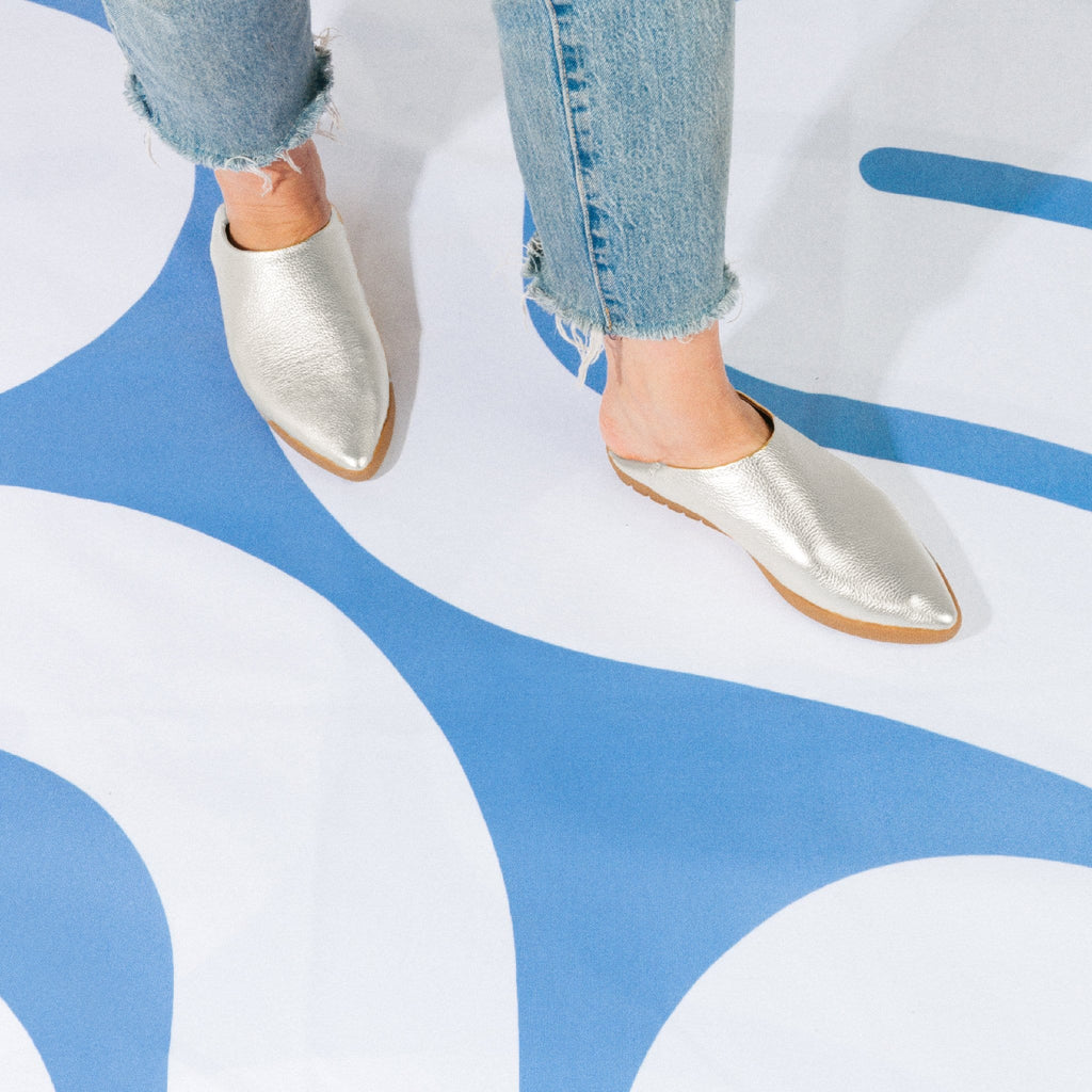 Silver metallic pebble grain shoes shown on legs wearing light blue denim jeans.  Model is walking on a blue and white labyrinth.