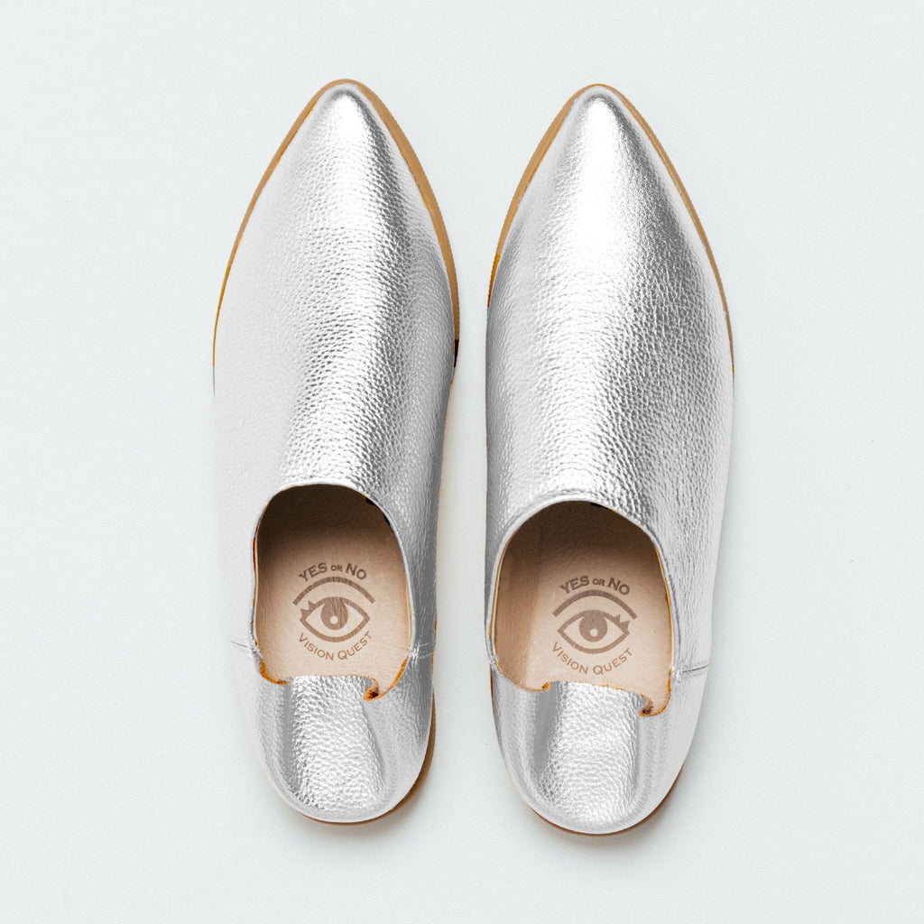 Overhead view of one pair of silver metallic pebble grain babouche sneakers with pointy toes.   Beige colored leather lining is visible with Vision Quest logo with one eye on each shoe, creating a pair of eyes together.  Both shoes are shown with the back heel part folded down.