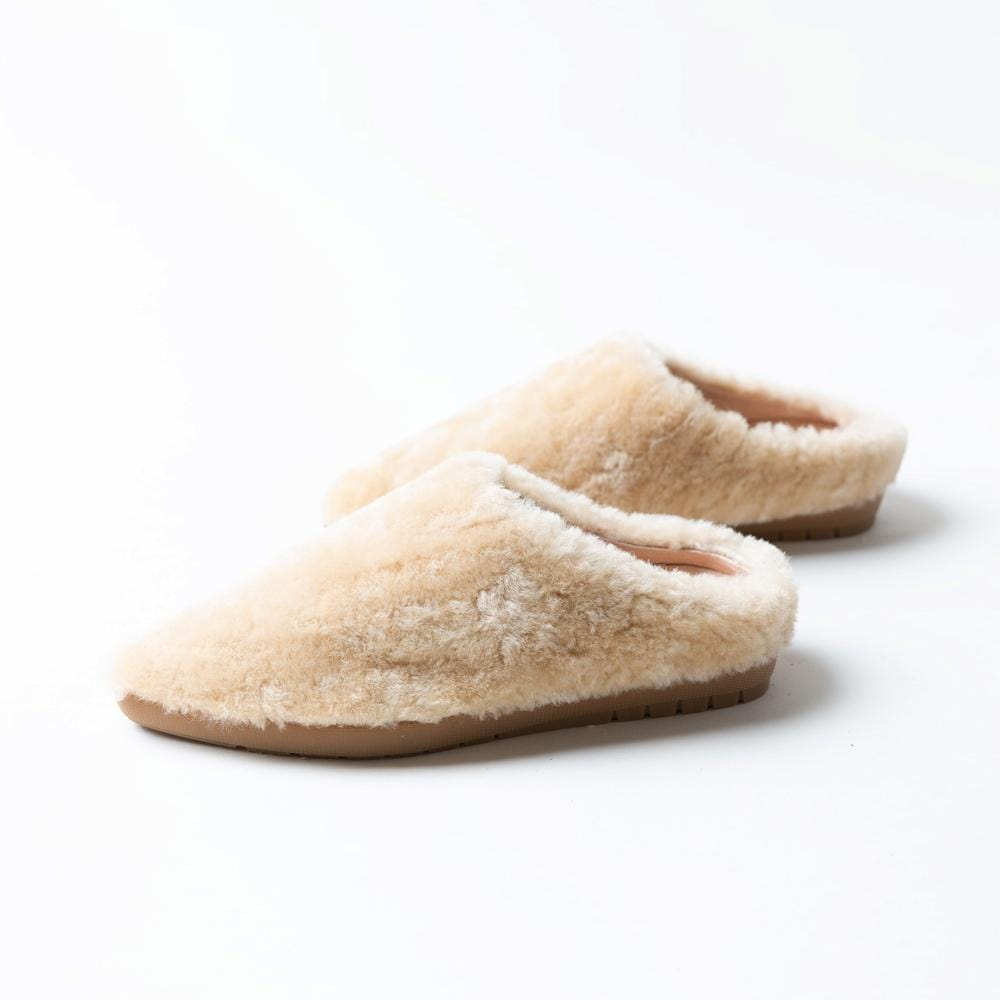 Profile view of Vision Quest Shoes beige shearling leather lamb shoes also known as babouche sneakers.  The toe shape of shoes are pointed and the shoes are flat.  The outsoles are made of rubber like a sneaker. The shearling texture is varied and fluffy, like a teddy bear.
