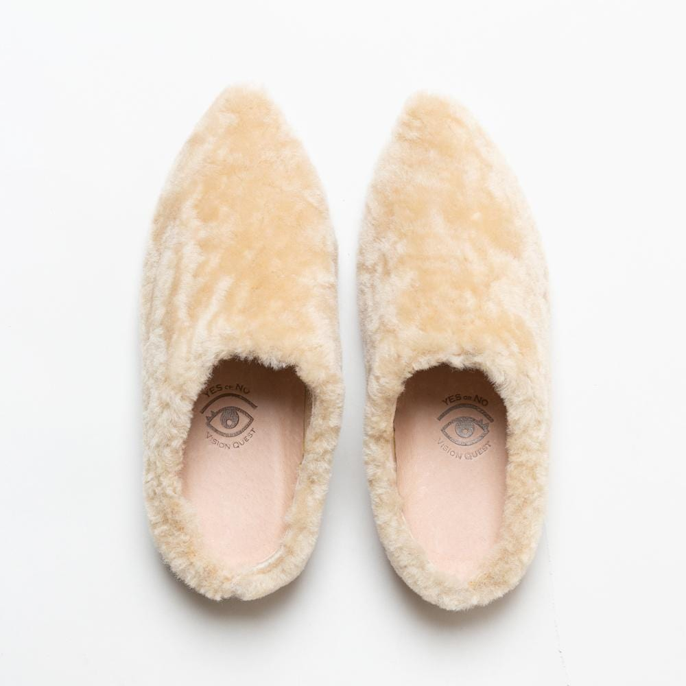 Overhead view of one pair of Vision Quest Shoes beige shearling leather lamb babouche sneakers with pointy toes. Beige colored leather lining is visible with Vision Quest logo with one eye on each shoe, creating a pair of eyes together.