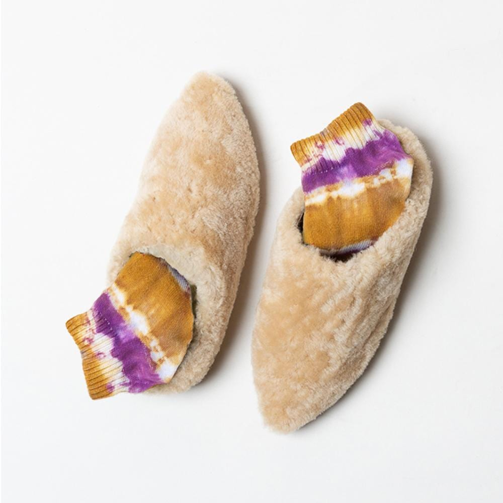 Overhead view of one pair of Vision Quest Shoes beige textured leather lamb  babouche sneakers with pointy toes.  Dark pink and golden yellow tie dyed socks are shown inside each shoe.