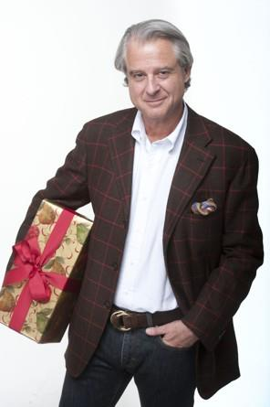 Adam Mahr, owner of A Mano, holding a gift wrapped present