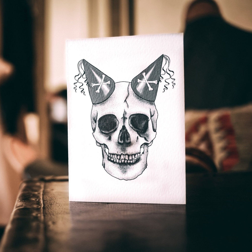 A6 White Greetings card with Skull design with 2 party hats by Wayward