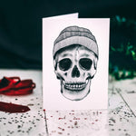 Greetings card with illustrated grey skull with beanie hat