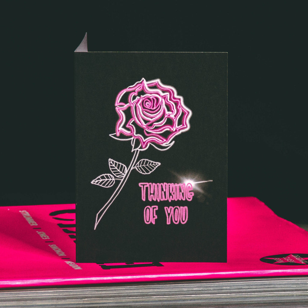 A6 Black Greetings Card With Pink Neon Tattoo Style Rose and Thinking of You text by Wayward