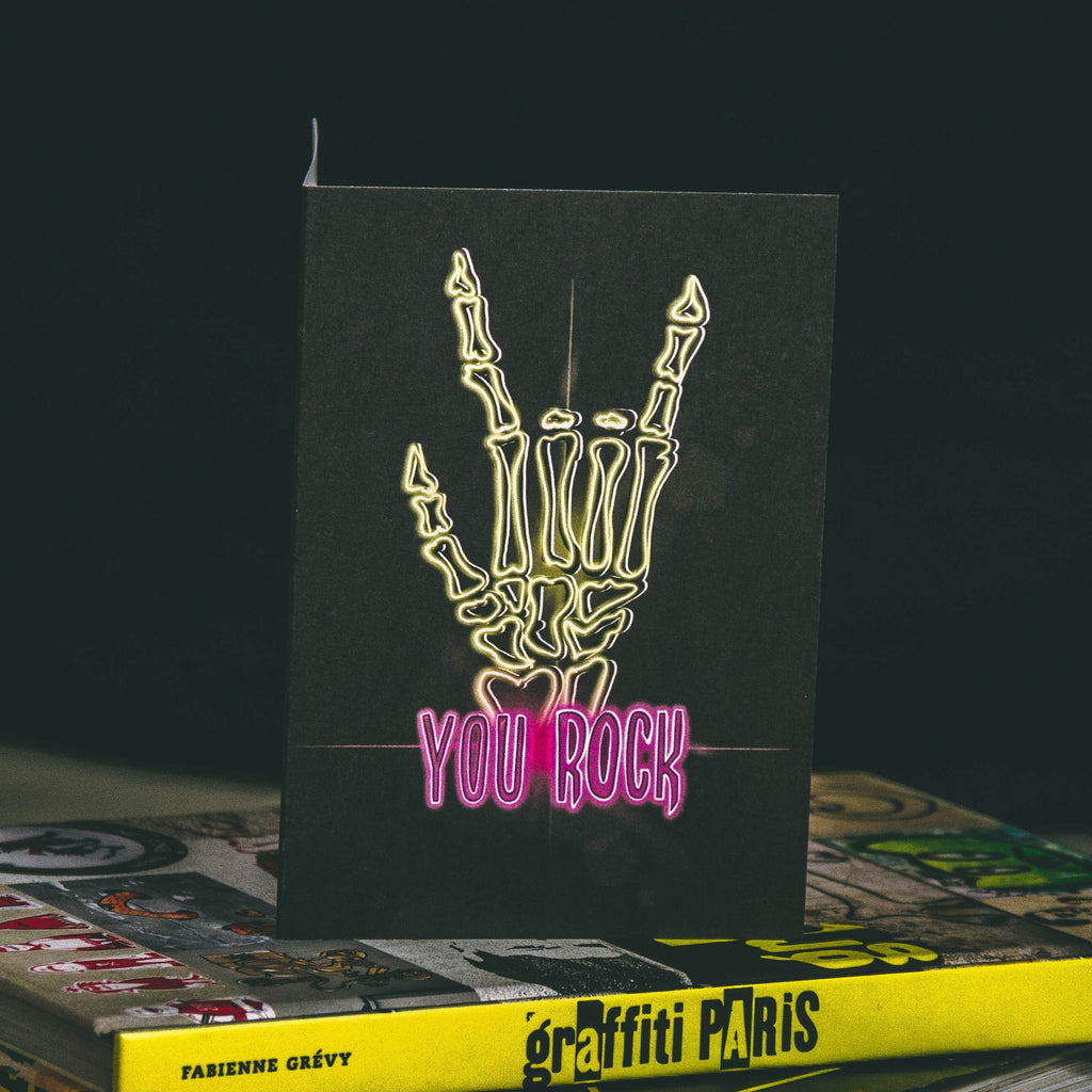 A6 Greeting Card with yellow neon skeleton rock hand and pink you rock writing by wayward