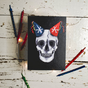 Flatlay of Black Birthday Card with Illustration of skull wearing party hats as horns