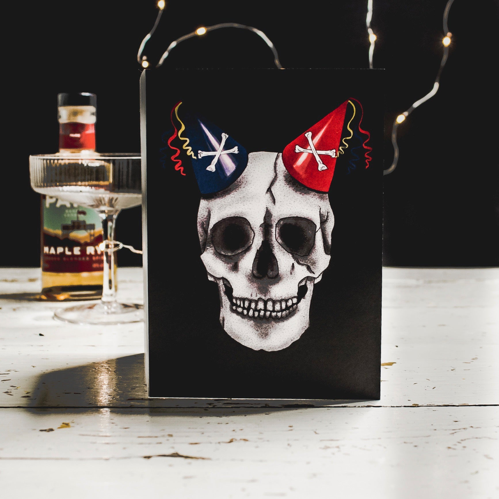 Black Birthday Card with Illustration of skull wearing party hats as horns