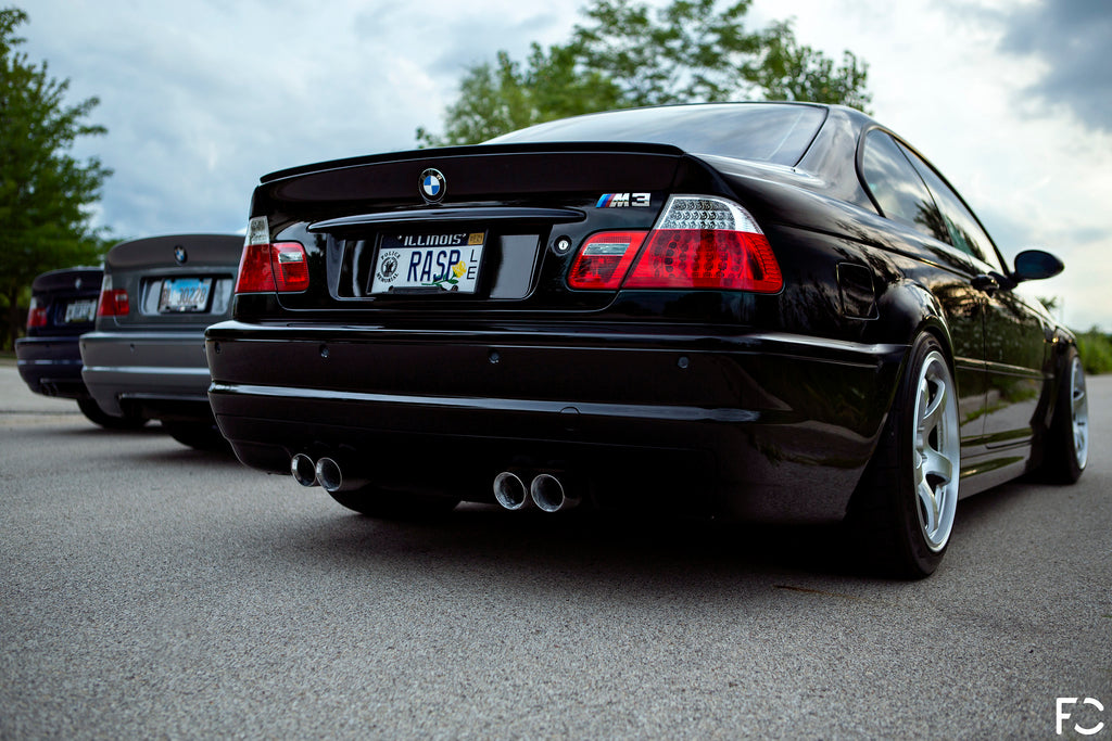 Jet Black E46 M3 rear angle low shot with OEM chrome trunk emblem