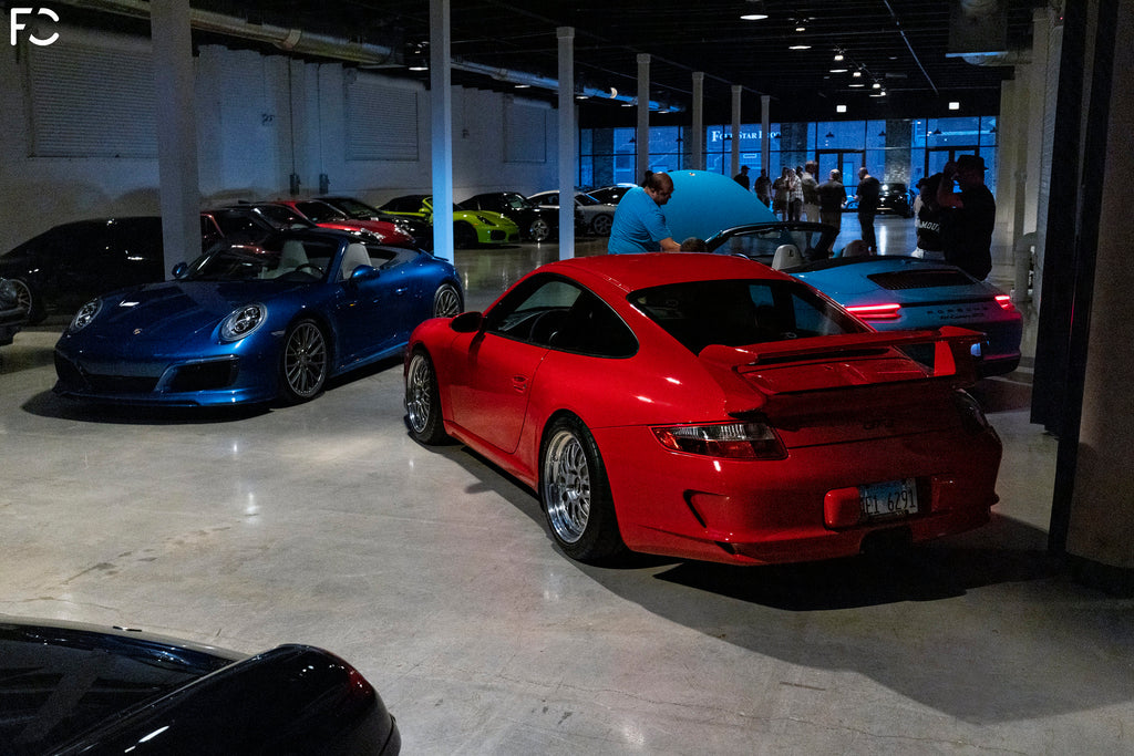 Rear angle view of Future Classic 997 GT3 surrounded by Porsches inside Revel event space in Chicago