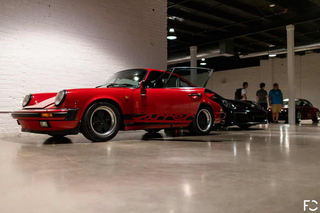 Side view of red Porsche 911 G-Body parked inside the Revel event space in Chicago