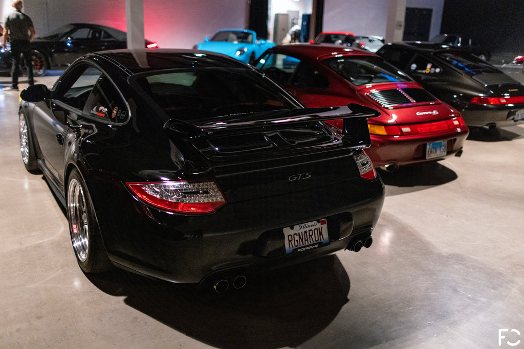 Rear view of a trio of 997 and 964 Porsches parked inside the Checkeditout event space