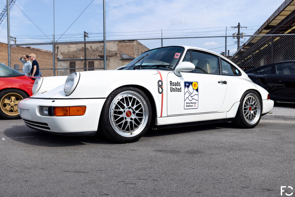 Front angle photo of the RoadsUnited white Porsche 964 on BBS LM wheels