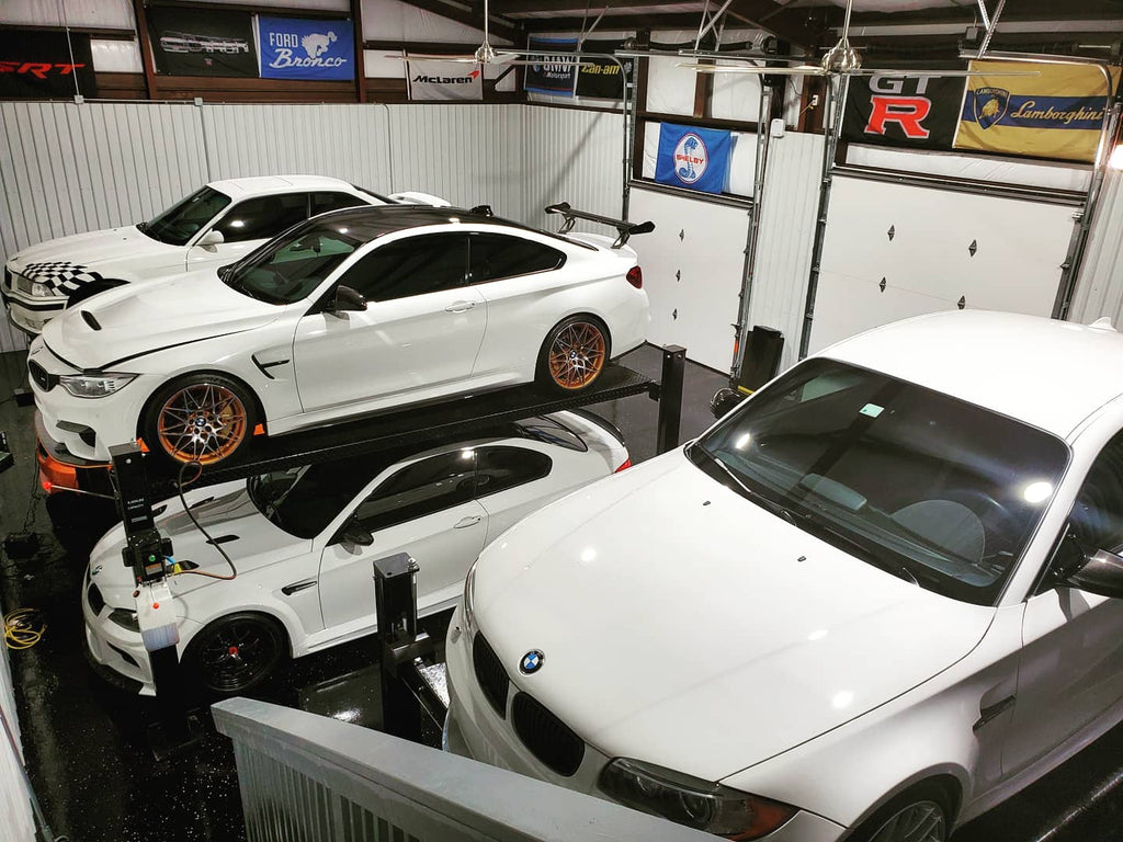 Ultimate Modern BMW M Garage - Top view from stairs looking down on lifts - M4 GTS