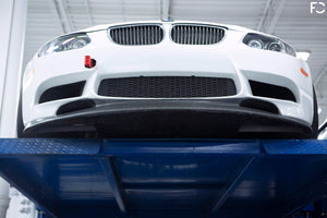 Front underside view of the Fall-Line Motorsports carbon lip to illustrate lip channeling and NACA ducts against the OEM BMW E9X M3 bumper
