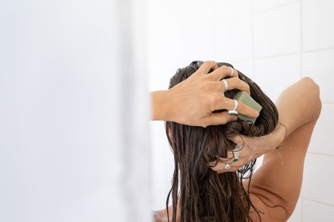Woman washing her hair with an all natural zero waste shampoo bar.