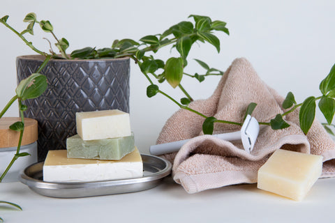 All natural shampoo bars on a table with plants and plastic free razors