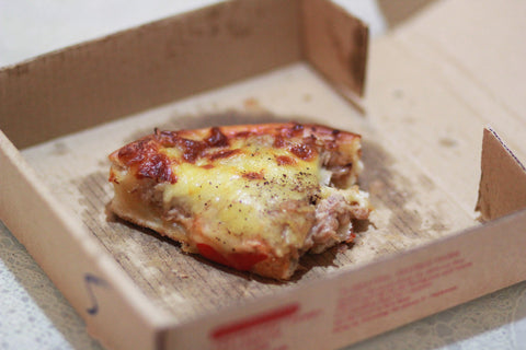 Greasy pizza box with slice of pizza