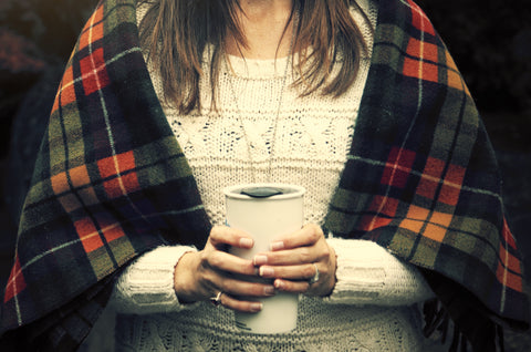 Woman holding reusable coffee mug