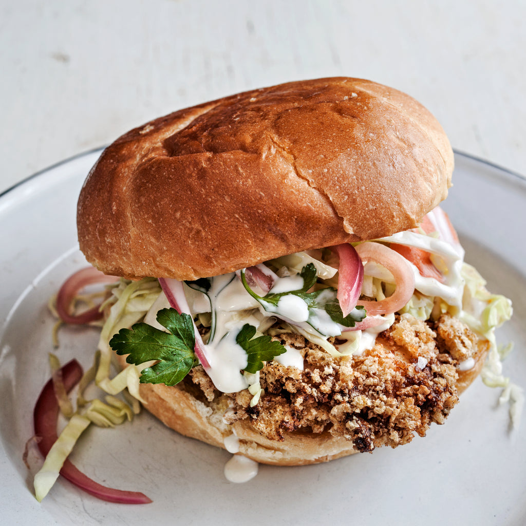 Fried chicken sandwich on a bun with coleslaw and white sauce