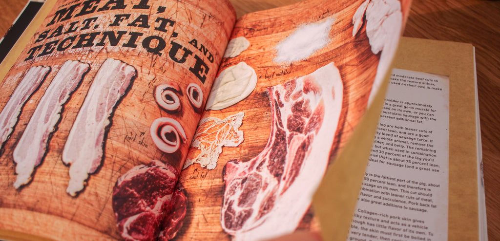 An open copy of our Sausage Making book with pictures of different cuts of meat and parts of the animal used for sausage making.