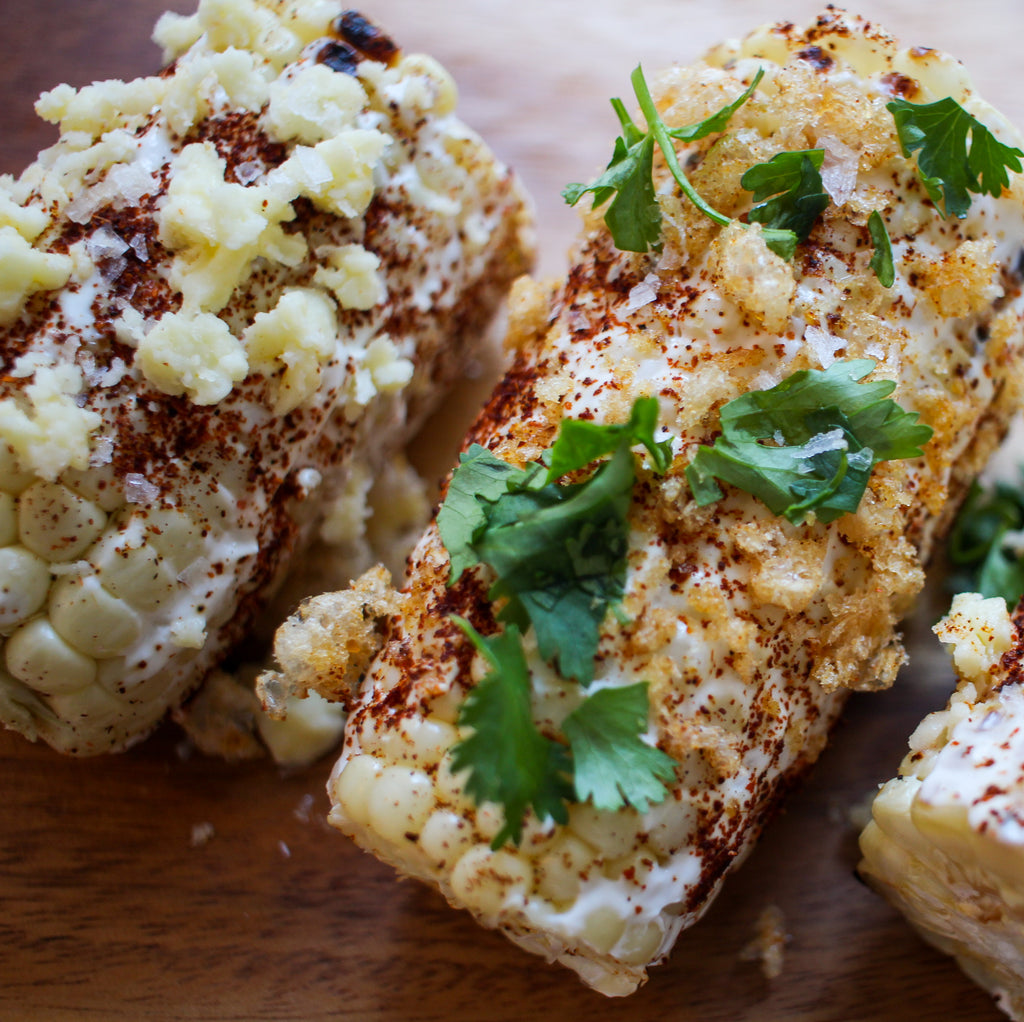 Corn on the cob slathered with mayo, chili powder, grated cheese and crumbled chicharrones