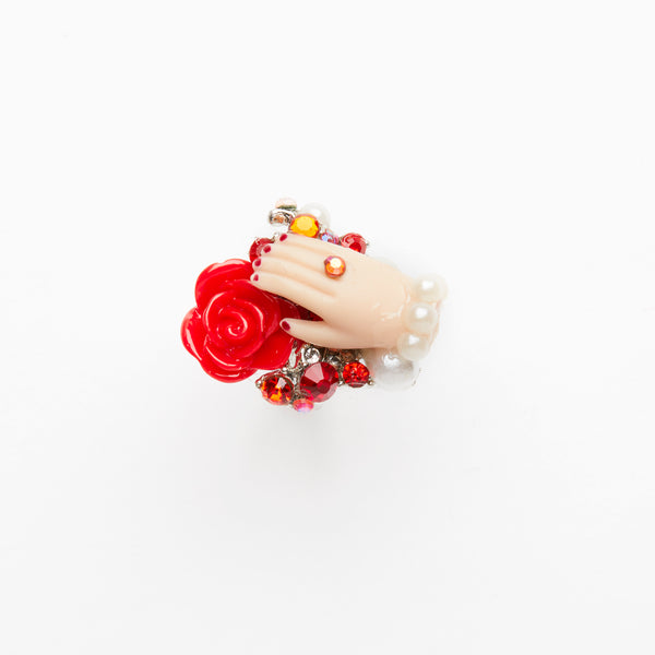 Doll hand ring on red flowers