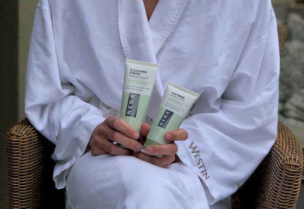 woman in bath robe holding Nena Clay Mask and Nena Cleansing Cream, Travel-based skincare tips