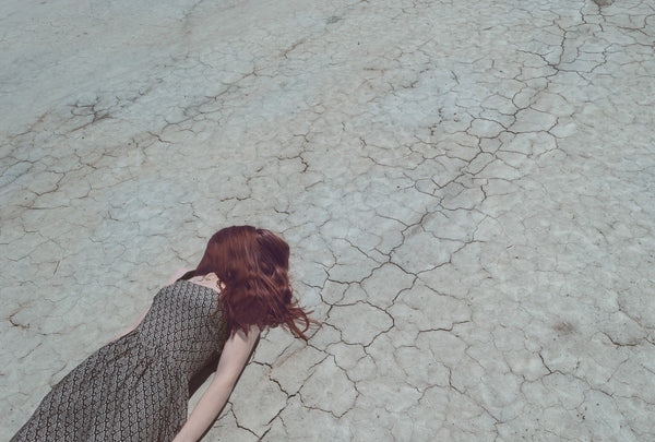 woman laying on dry ground